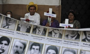 Indigenous people hold crosses in front portraits of disappeared people during a demo for the advance of investigations in cases of genocide at court in Guatemala City