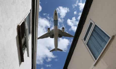 A passenger jet comes in to land over houses next to Heathrow airport.