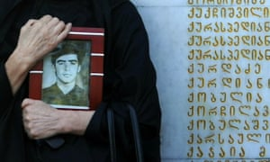 A woman holds a portrait as she mourns at a memorial to those killed during the 1992-1993 Georgia-Abkhazia armed conflict at a ceremony marking the annual anniversary of the event in Tbilisi.