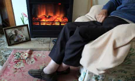 Elderly man at home in front of fire