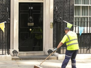 A street cleaner sweeps outside No 10 Downing Street in central London