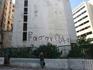 """A man stands in front of a building with a graffiti that reads """"I'm being tortured"""" in central Athens September 3, 2012."""