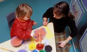 Teacher and child in nursery UK