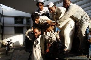 24 hours: Jalalabad, Afghansitan: An injured Afghan man is helped