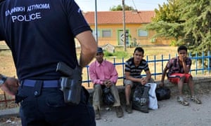 A police officer guards illegal immigrants in northern Greece