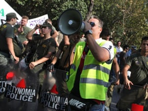 A protesting police officer shouts slogans through a megaphone in front of riot police outside police facilities at Zografou, northeast of central Athens, on Thursday, Sept. 6, 2012.