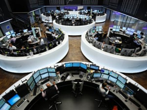 Traders works at their desks at the Frankfurt stock exchange this morning.