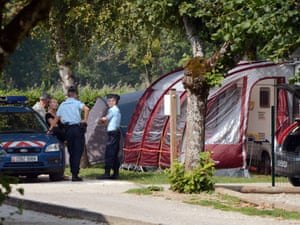 """French gendarmes talk with investigators near the caravan of the British family attacked by a gunman in the camping """"Le Solitaire du lac"""" in the French Alpine village of Saint-Jorioz."""