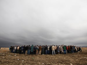 Striking mineworkers hold a meeting near Lonmin's Marikana mine in South Africa's North West Province, this morning.