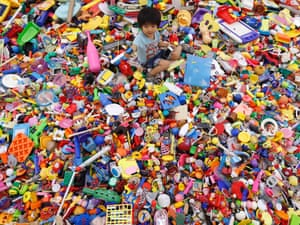 A boy plays on an artwork made of unwanted toys at the solo exhibition of Japanese artist Hiroshi Fuji, known for his creations that recycle unwanted toys and waste materials, in Tokyo today.