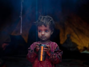 Saleena Khan, a Bakarwal nomad child holds a mug in a temporary camp in Kangan, a small town about 25 miles north east of Srinagar, India. Bakarwals are nomadic animal herders in Jammu Kashmir state, who travel in search of good pastures for their cattle.
