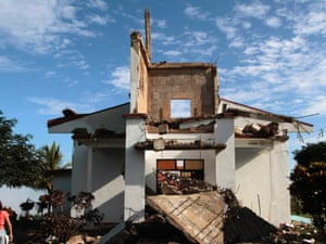 A resident of Bella Vista town takes a picture with her cellphone outside the church destroyed by an earthquake in Nicoya today. Costa Rica escaped relatively unscathed after a powerful earthquake hit the country on Wednesday, sparking landslides and knocking down buildings without killing anyone.