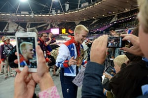 100m final batch 3: Fans take photographs of Great Britain's Jonnie Peacock