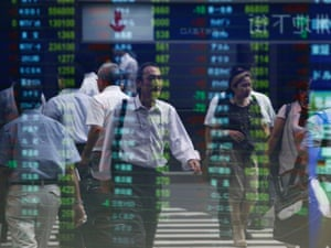 Passers-by are reflected on an electronic monitor displaying share prices at a brokerage in Tokyo September 7, 2012.
