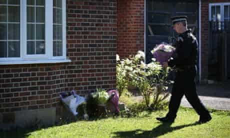 A police officer carries flowers across the lawn to the house the al-Hilli family