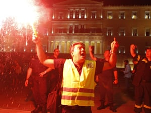 A protesting officer from Greece's coast guard holds a flare in front of parliament during an anti-austerity protest. More than 4,000 officers, chanting 'thieves, thieves' and carrying black flags took part in the march against expected new pay cuts in the crisis-hit country.