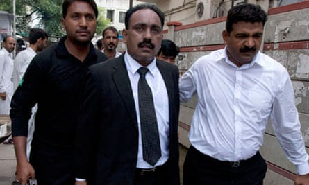Tahir Naveed Chaudhry, a lawyer for Rimsha Masih, leaves court with an armed escort