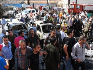 Syrian security forces and people inspecting the site of a car bomb blast in the Mazzeh area of Damascus on September 7, 2012. A car bomb struck the upscale area of Damascus, near the central law courts and ministry of information, state TV reported just two hours after a first bomb attack in the north of the capital.