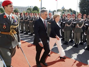 German chancellor Angela Merkel and her Austrian counterpart Werner Faymann review the honour guard during her official visit to Austria on September 7, 2012 in Vienna.