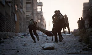 Rebel soldiers help a severely wounded colleague in Izaa district in Aleppo, Syria