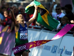 Tito Sena waves the Brazilian flag as he crosses the line to win the T46 marathon on The Mall
