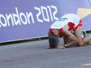 Spain's Alberto Suarez kisses the tarmac after winning the T12  marathon