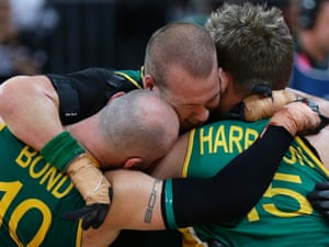 Ryley Batt, Chris Bond and Andrew Harrison of Australia hug after defeating Canada in the gold medal wheelchair rugby match
