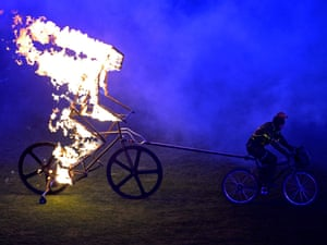 A flaming figure of a cyclist is towed into the arena