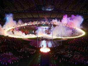 Flag-bearing athletes stand within a ring of fire  shaped like a heart.