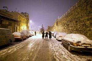 Snow in Jerusalem: Ultra-Orthodox Jewish boys walk down a snow-covered street