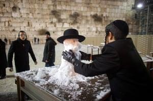 Snow in Jerusalem: An ultra-Orthodox Jewish boy builds a snowman