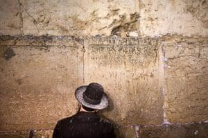 Snow in Jerusalem: An ultra-Orthodox Jewish man prays as snow falls