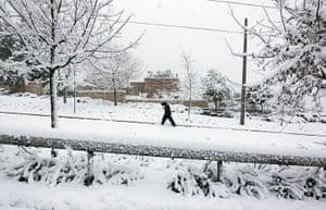 Snow in Jerusalem: A pedestrian walks on a snow-covered street in east Jerusalem