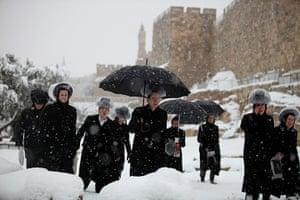 Snow in Jerusalem: Ultra-Orthodox  Jews walk along the Old City walls