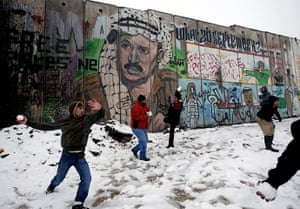 Snow in Jerusalem: Palestinians play in the snow next to a section of Israel's barrier