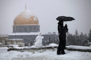 Snow in Jerusalem: A Palestinian man stands on a roof of a house near the Dome of the Rock