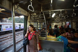 Trains for women: A woman speaks on the phone as she stands near the open doorway
