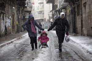Snow in Jerusalem: A girl enjoys sledging on an icy road