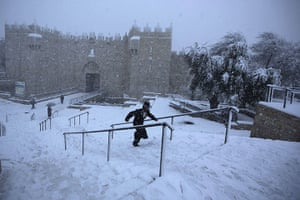 Snow in Jerusalem: An ultra-Orthodox Jewish man runs as snow falls