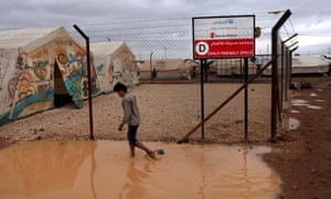 A Syrian refugee boy makes his way through water and mud, next to a Unicef school at Za'atari Syrian refugee camp, near the Syrian border in Mafraq, Jordan. Syrian refugees in a Jordanian camp attacked aid workers with sticks and stones on Tuesday.