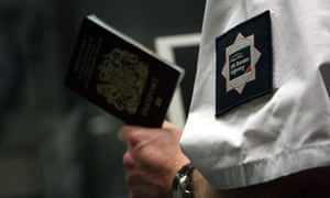 A UK Border Agency officer checks a passport at Gatwick airport, Sussex.