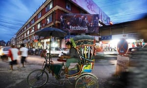 A rickshaw driver sits on his rickshaw while he waits for passengers along the streets of Kathmandu