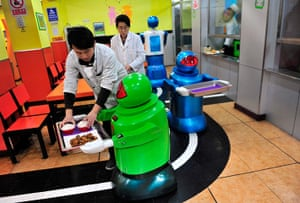 Robot Restaurant: Human waiters assist the robots in loading the trays of food