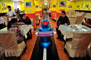 Robot Restaurant: A 'waiter' robot holds an empty tray after serving meals to the customers