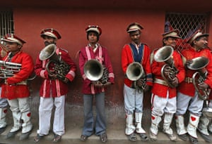 24 hours: Members of a brass band wait for a religious procession to start