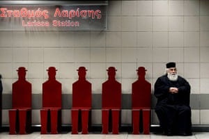 24 hours: A Greek Orthodox priest sits on a train platform