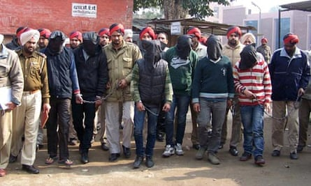 Police with rape suspects arrested with faces covered