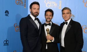 Actor and director Ben Affleck, left, producer Grant Heslov, centre, and producer George Clooney pose with the Golden Globe for best motion picture for Argo.