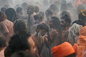 Kumbh Mela: Naked Hindu holy men or a Naga Sadhus dry their hairs after a dip at Sangam