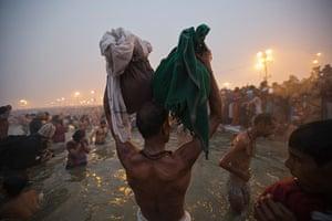 Kumbh Mela: A Hindu devotee holds his belongings aloft